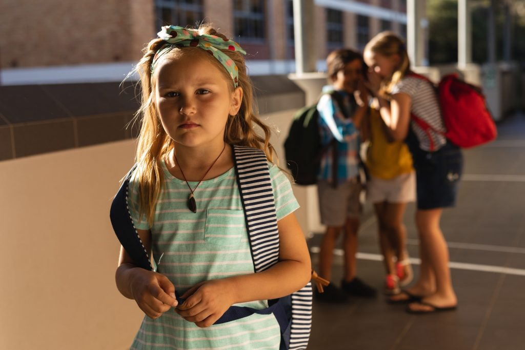 School friends bullying a sad girl in hallway of elementary school