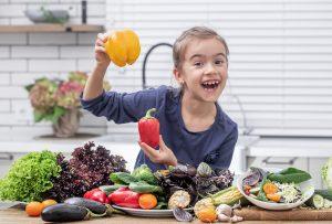 petite fille souriante avec des légumes