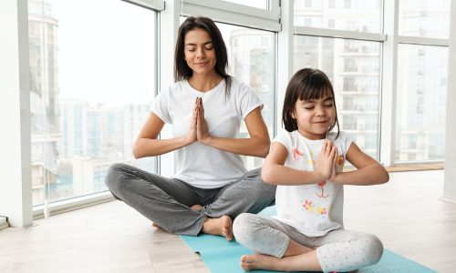 Beautiful mother and child meditating at home, sitting legs cros