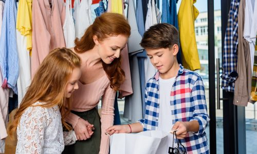 mother and children shopping in stylish boutique