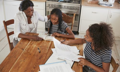 Mother Helping Two Daughters Sitting At Table Doing Homework