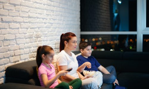 Single Mother And Children Watching TV At Night